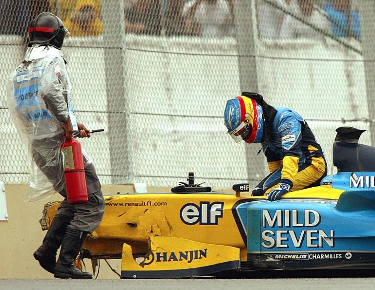 Alonso klifrar úr Renault-bíl sínum eftir árekstur í Brasilíu 2003.