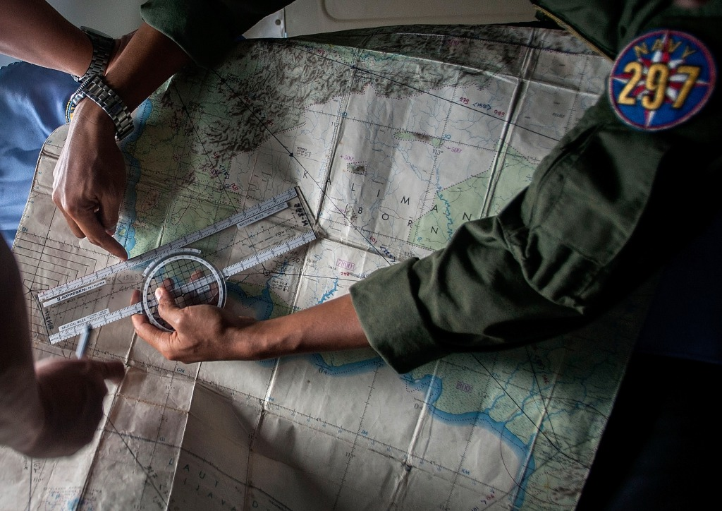 Indonesian Army personnel read a map during a search and rescue (SAR) operation for missing Malaysian air carrier AirAsia flight QZ8501, over the waters of the Java Sea on December 29, 2014. Multinational teams searched on December 29 for any sign of the AirAsia plane missing off Indonesia with 162 people on board, but one top official warned it was likely at the bottom of the sea.    AFP PHOTO / Juni KRISWANTO