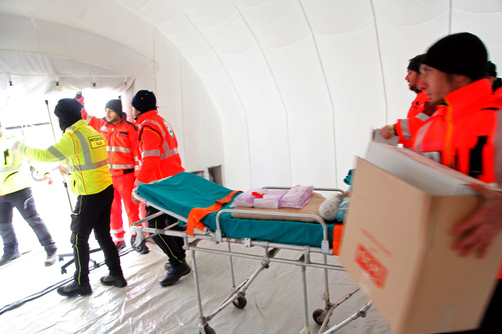 """Italian Red Cross volunteers set up a tent camp to accommodate the rescued passengers of  the """"Norman Atlantic"""" ferry, in the port of Manfredonia, southern Italy, on December 30, 2014. Ten passengers dead, dozens unaccounted for and no-one able to say with any certainty how many people were on board the Norman Atlantic when it burst into flames. A Greek ferry tragedy in the Adriatic turned into a murder mystery on December 30 as a fiasco over the accuracy of the passenger list added to questions over safety systems aboard. The maltese cargo Aby Jeannette with some of the rescued passengers aboard could not reach the port of Manfredonia due to bad weather, and was routed by the italian Coast Guards towards Taranto harbour. AFP PHOTO / CARLO HERMANN"""