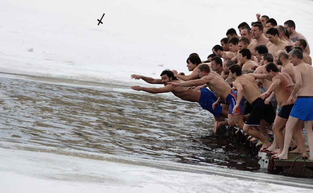 Bulgarian men jump into the waters of a lake to recover a wooden cross during the Epiphany day celebrations in Sofia.